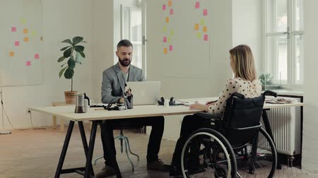 коллега : Two business people with wheelchair in the office. Стоковые видеозаписи