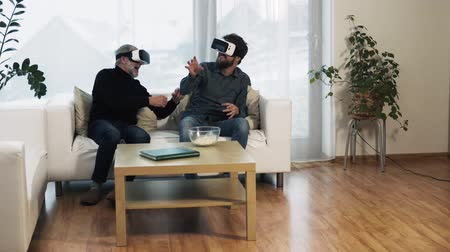 tüy : Hipster son and his senior father with VR goggles at home. Stok Video
