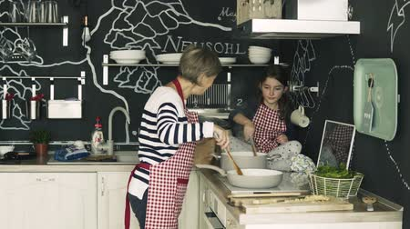шпинат : A small girl cooking with grandmother at home. Стоковые видеозаписи