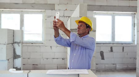 housing problems : Senior architect with smartphone at the construction site.