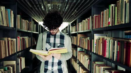 checked pattern : Young male student studying in a library.