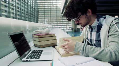 checked pattern : Young student with laptop and headphones in a library. Stock Footage