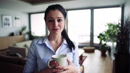 termostat : Woman holding cup of coffee in living room. Smart home.