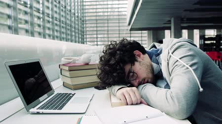 старшей школе : Young student with laptop and headphones in a library, sleeping.