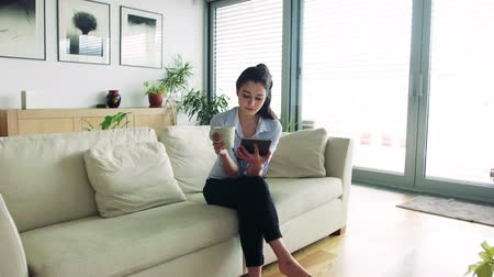 termostat : Woman with tablet in living room. Smart home.