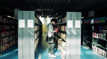 checked pattern : Young male student walking in a library. Stock Footage