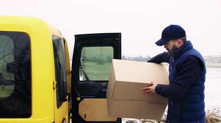 recipient : Delivery man with smartphone delivering parcel box to recipient. Stock Footage