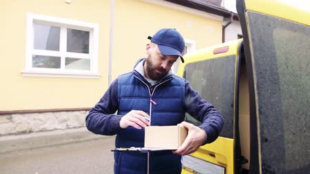 доставка : Delivery man delivering parcel box to recipient.
