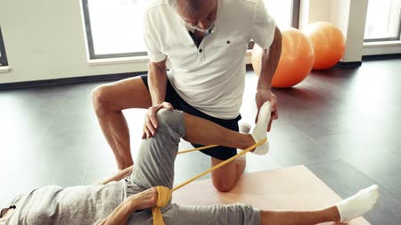 fizjoterapeuta : Senior physiotherapist working with a female patient.