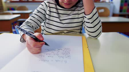 A small girl at the desk at school, writing. Стоковые видеозаписи