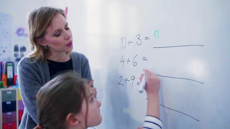 A small girl with teacher writing on the whiteboard at school. Стоковые видеозаписи
