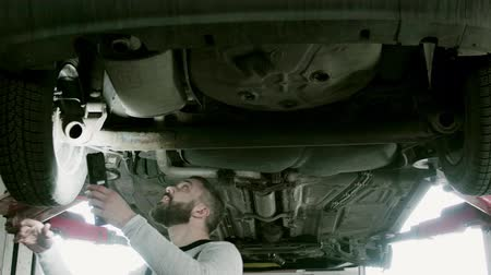 Man mechanic repairing a car in a garage. Стоковые видеозаписи