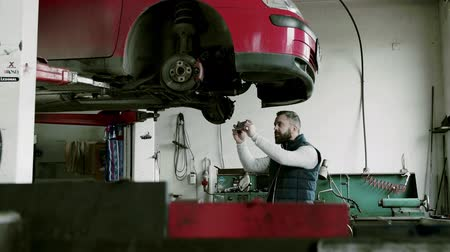 Man mechanic with smartphone repairing a car in a garage. Стоковые видеозаписи