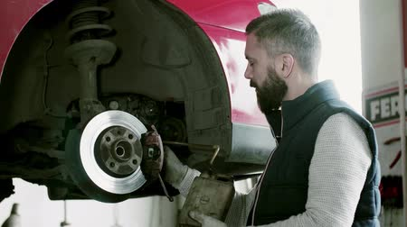 fixing : Man mechanic repairing a car in a garage. Stock Footage