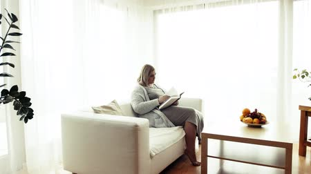 An attractive overweight woman at home, reading a book.