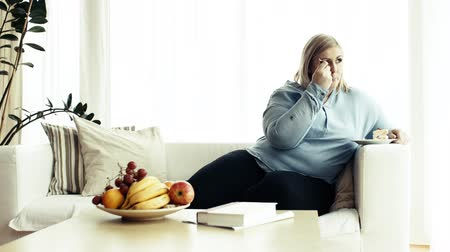 An attractive overweight woman at home, eating cake. Vídeos