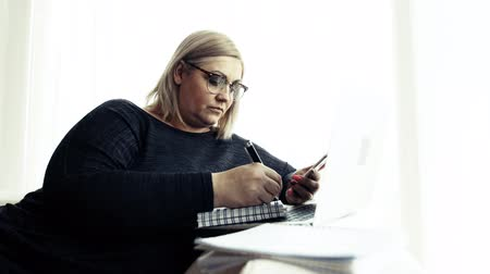 An attractive overweight woman at home, using smartphone and laptop.