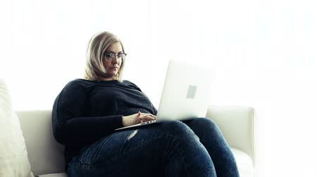 An attractive overweight woman at home, using laptop.
