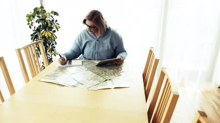 An overweight woman at home, sitting at the table with tablet and map. Vídeos