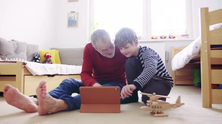Senior grandfather and a small grandson with tablet playing at home. Стоковые видеозаписи