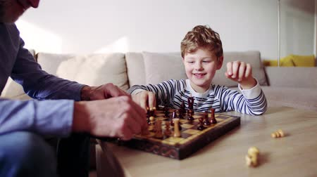 Senior grandfather with a grandson playing chess at home. Стоковые видеозаписи