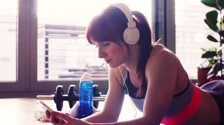 hareketli : Young fitness woman with smartphone and headphones at home.
