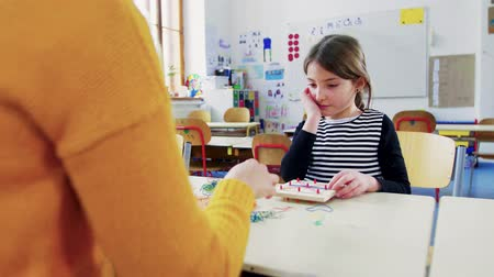 intézmény : A small girl with teacher learning at school.