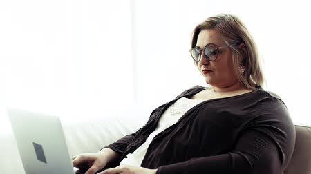 tvaru srdce : An attractive overweight woman at home, using laptop.
