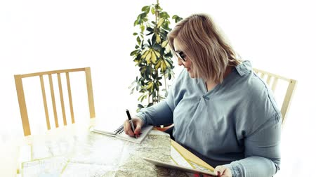 An overweight woman at home, sitting at the table with tablet and map. Стоковые видеозаписи