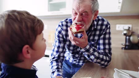 checked pattern : Senior grandfather with small grandson eating at home.