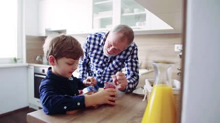 Senior grandfather with small grandson preparing food at home. Стоковые видеозаписи