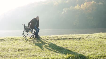 Senior man with wheelchair in autumn nature. Стоковые видеозаписи