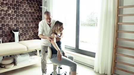 rehabilitasyon : Senior man physiotherapist working with a female patient.