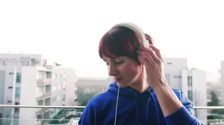 blocks of flats : Young fitness woman with headphones on a balcony at home. Stock Footage