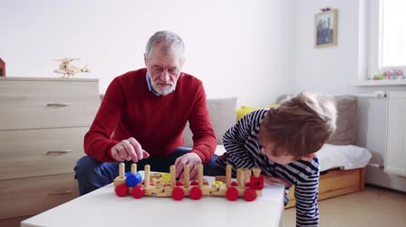 blok mieszkalny : Senior grandfather with a small grandson at home playing.