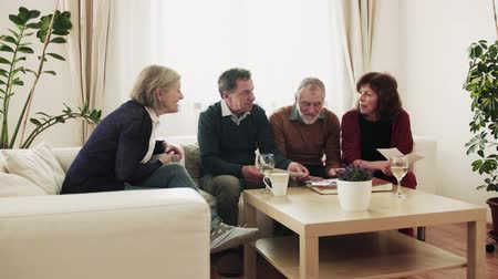 coffee house : Two senior couples looking at photographs at home. Stock Footage