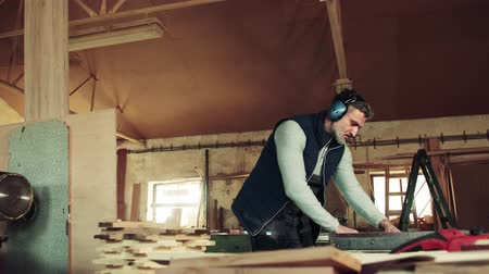 craftsperson : A man worker in the carpentry workshop, working with wood. Stock Footage