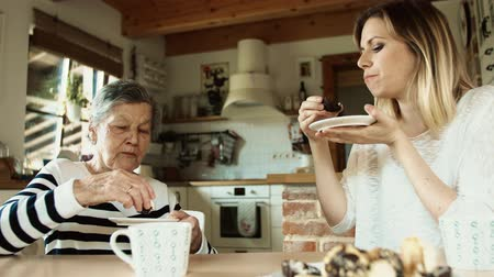 полосатый : Elderly grandmother with an adult granddaughter eating biscuits at home.