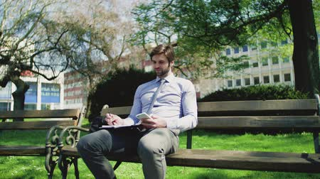 sucessful : A young businessman with smartphone outside in city, sitting on bench, writing.