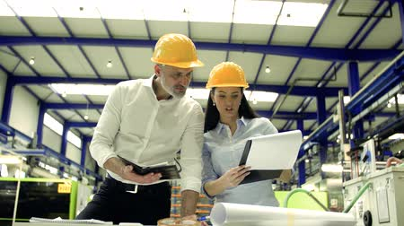 vest : Industrial man and woman engineers with clipboard in a factory, working.