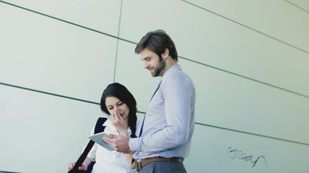 white shirt : Young businessman and businesswoman with tablet outside in city, talking. Stock Footage