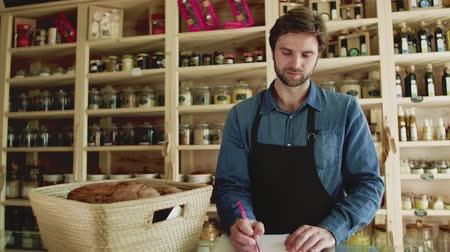 помощник : A young man shop assistant working in a zero-waste store or shop.