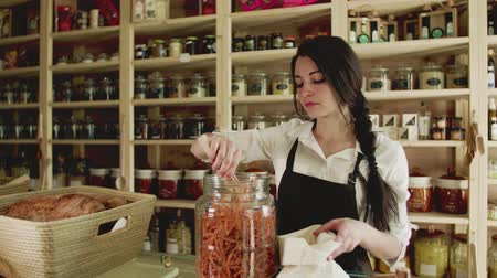 sklep spożywczy : A young woman shop assistant working in a zero-waste store or shop.