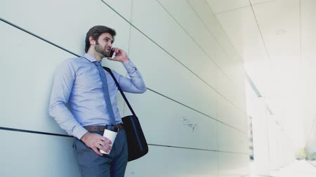 связать : A young businessman with smartphone outside in a city, making a phone call.