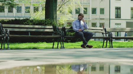 sucessful : A young businessman with smartphone outside in city, sitting on bench, making phone call.