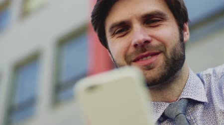 sucessful : Young businessman with smartphone sitting outside in city, texting. Close up.