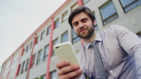 sucessful : Young businessman with smartphone sitting outside in city, texting.