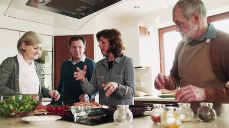 maso : Senior couple cooking dinner together with friends at home. Dostupné videozáznamy