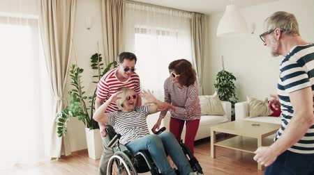 em forma de : Two senior couples with wheelchair dancing at the party at home, having fun.