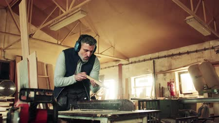 yelek : A man worker in the carpentry workshop, working with wood. Stok Video